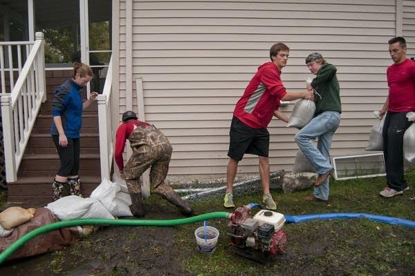 Volunteers help Sarah Rossi sandbag her house.