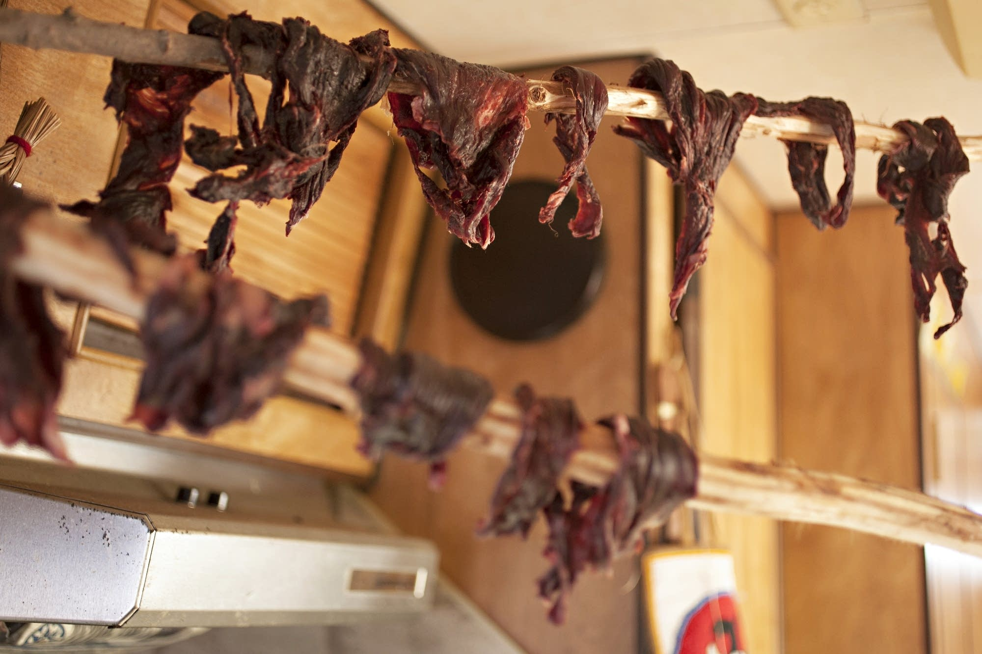 Strips of venison dry inside a small RV.
