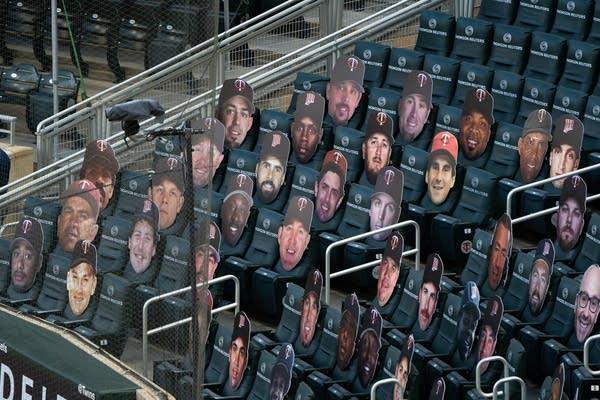Cardboard head cutouts in plastic seats.