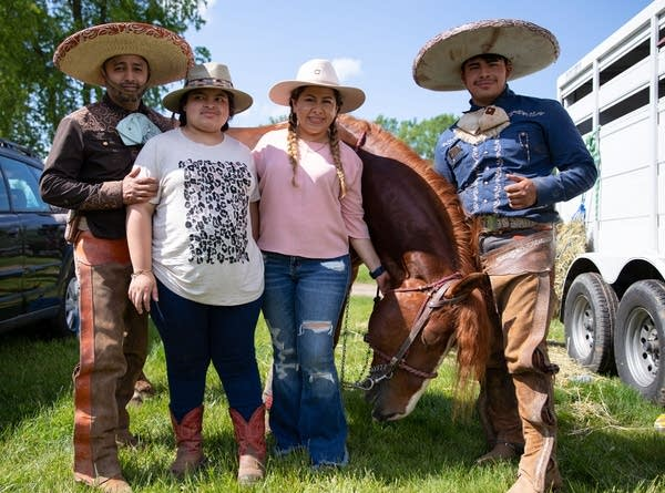 a family stands with a horse