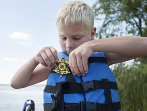 Gibbson Illg, 6, puts on a plastic badge before heading out to fish.