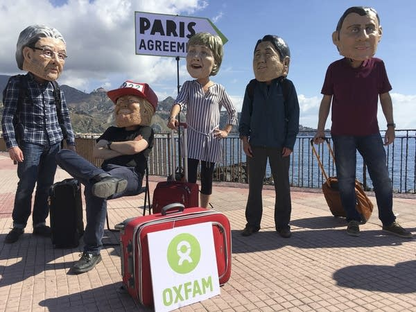Oxfam activists wearing masks of the leaders of the G7 summit