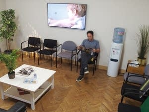 Omer Fast sits in the doctor's waiting room, the entrance to his show.