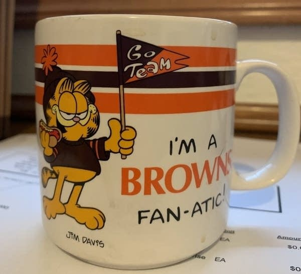 A mug featuring Garfield as a Cleveland Browns fanatic