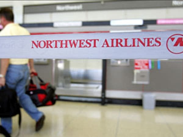 A traveler walks beyond Northwest Airlines signage