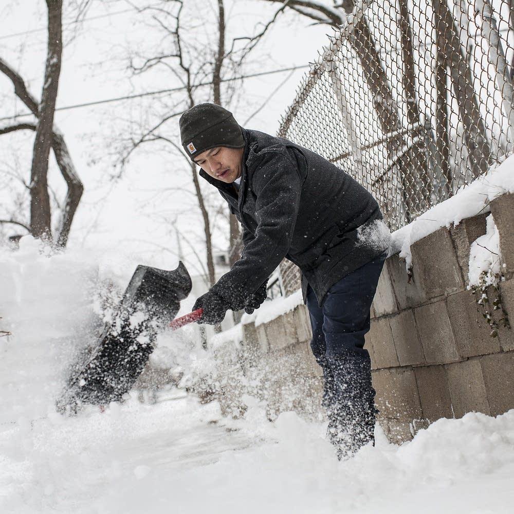Yupeng Yang shovels his sidewalk.