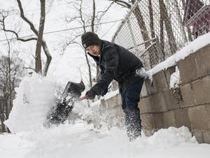 Yupeng Yang shovels his sidewalk.