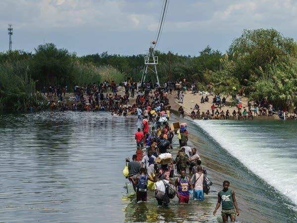 Migrants cross the Rio Grande