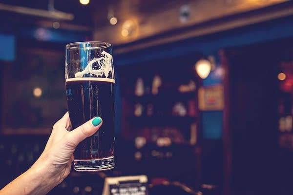A woman raises a glass of beer.