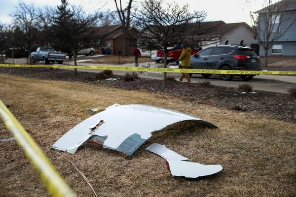 A piece of an airplane lays on grass, surrounded by police tape.