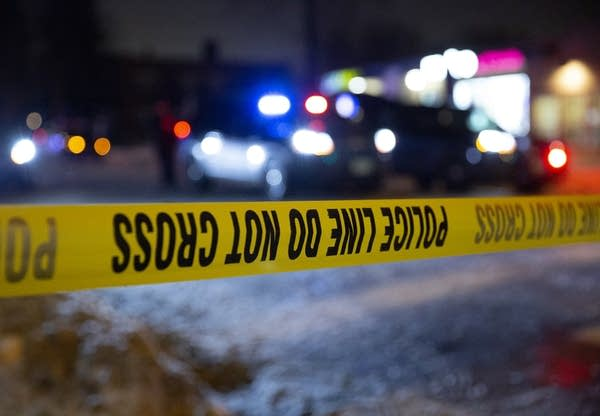 A photo of a yellow crime scene tape with police cars in the background.