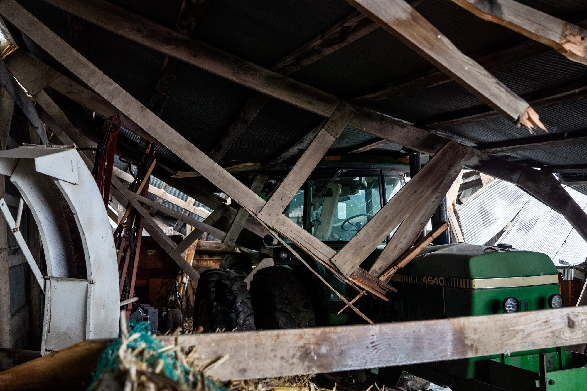 Totaled tractors are stuck in a collapsed machinery shed