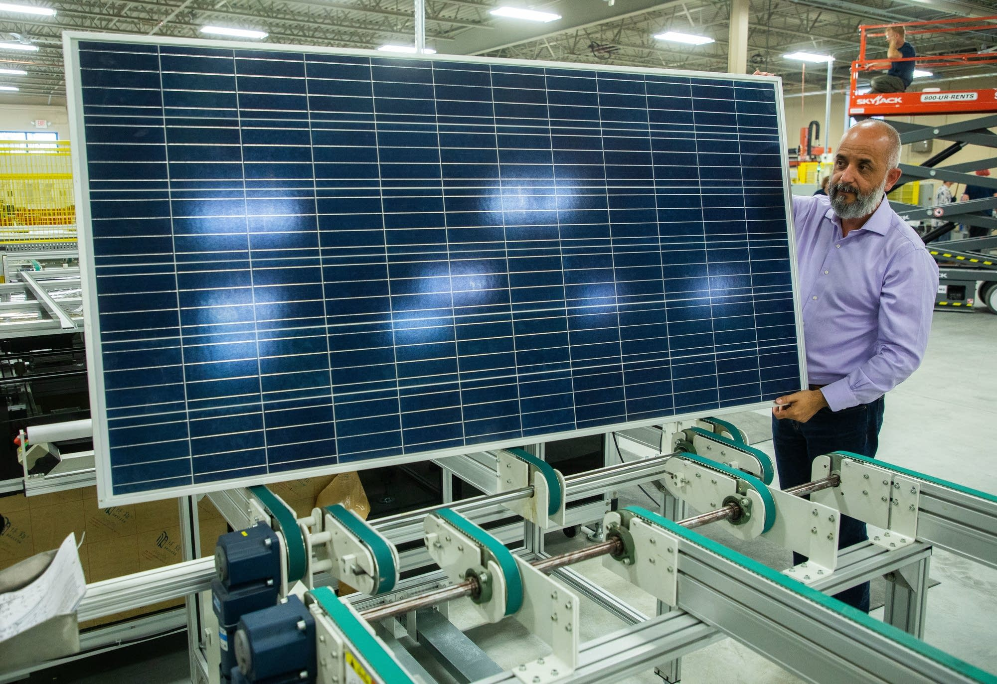 Heliene President Martin Pochtaruk holds up a completed solar panel.