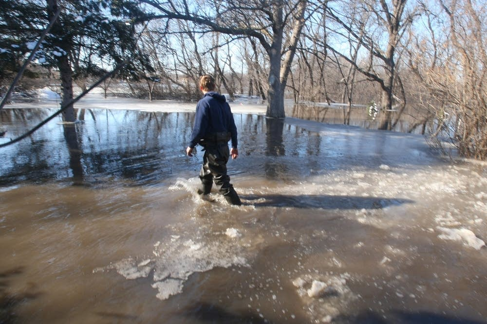 Jonathan Needham walks through a flooded yard