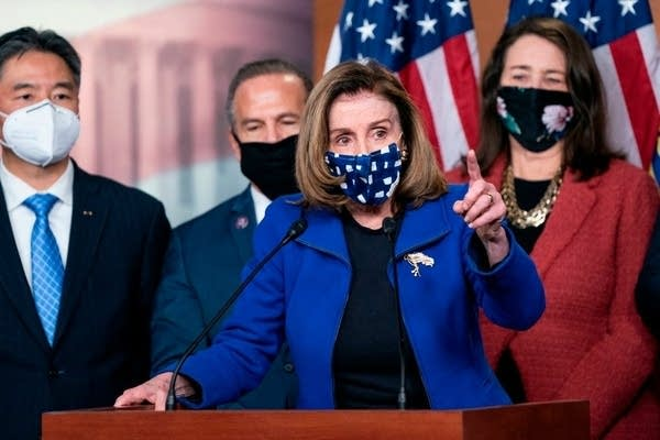 A woman in a mask speaks behind a podium, while others stand behind her.