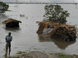 A man stands in floodwaters following cyclone-force winds and heavy rain.