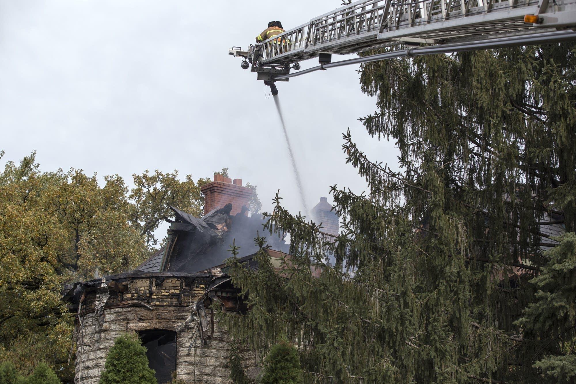 A St. Paul firefighter sprays down a historic house on Dayton Avenue.