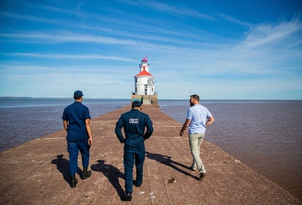 Three people walk to a lighthouse.
