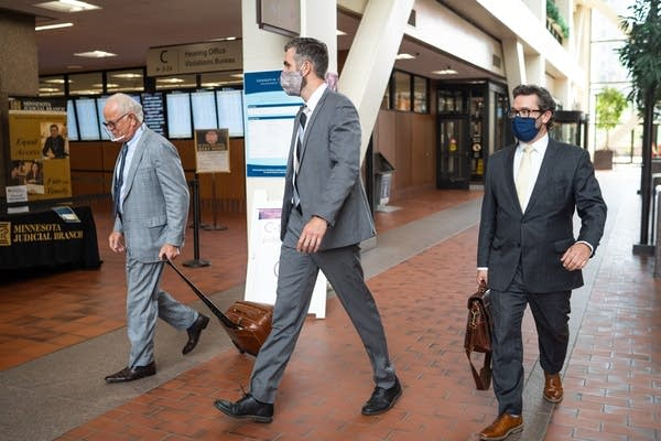 Three men walk in suits and masks.