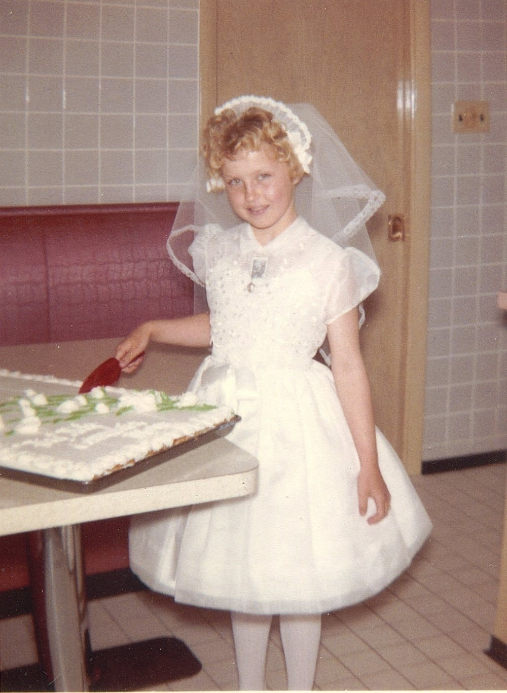 Mary Welke cutting her confirmation cake, 1962