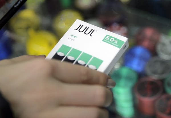 A woman buys refills for her Juul at a smoke shop