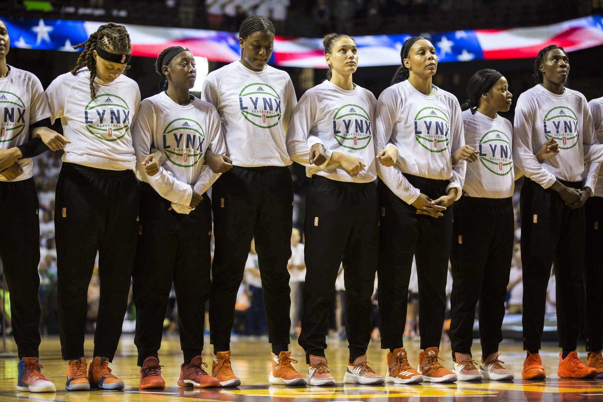 The Minnesota Lynx link arms during the national anthem.