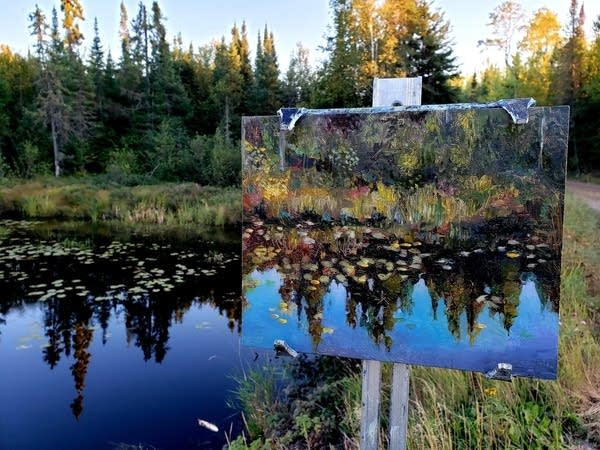 A painting of lily pads next to a pond.