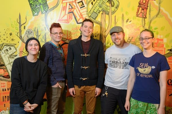Five people stand in front of a brightly painted wall.
