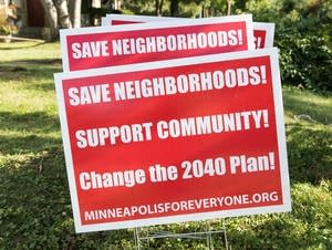 Signs opposing the Draft 2040 Comprehensive Plan sit in a front yard.
