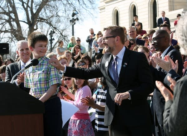 Jake Ross celebrates the signing of the law.