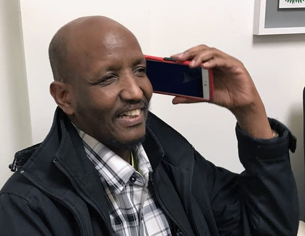 Mahamed Iye smiles as he speaks to his wife in Nairobi on his cell phone.