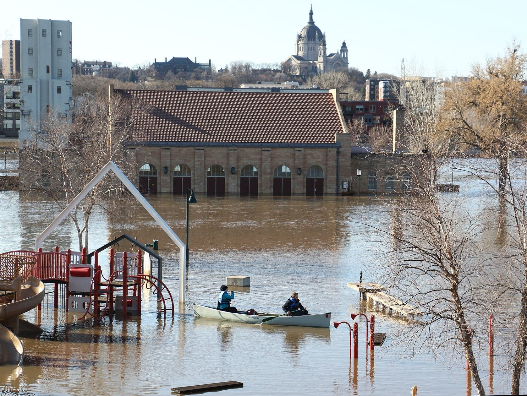 Canoeists paddle through a flooded playground at Harriet Island