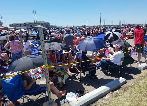 Trump supporters wait outside Scheels Arena in Fargo in the heat.