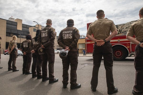 People in brown EMS jackets stand with their hands behind their backs.