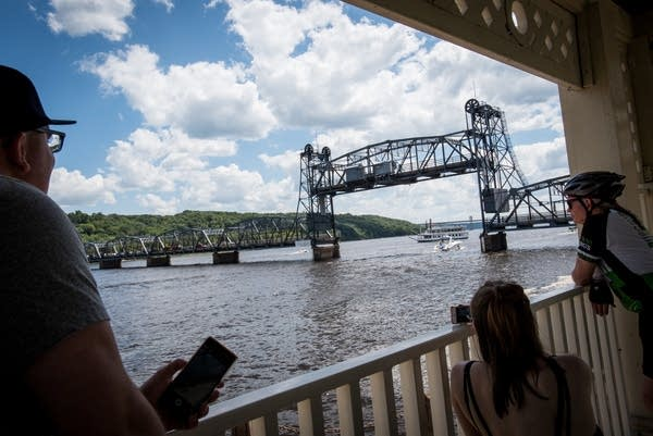 Spectators watch as the Stillwater Lift Bridge is raised for boats to pass.