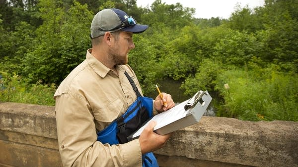 Fish biologist Chad Anderson records data on a bridge over Whitley's Creek.