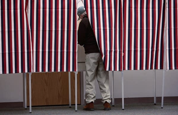A man marks his ballot in a voting booth