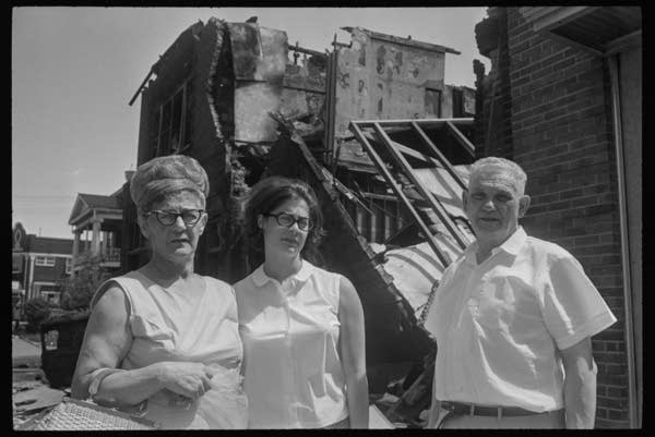 3 white people stand in front of a collapsed grocery store.