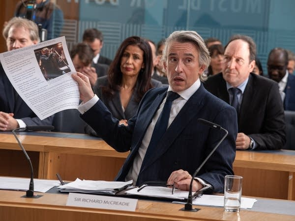 A man holds up a document in a government hearing.