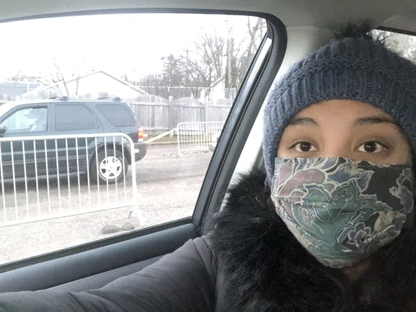 A woman wearing a face mask takes a selfie in a car.