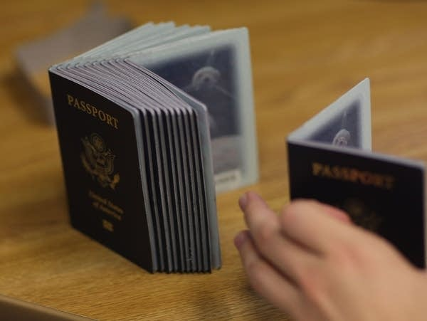A Passport Processing employee uses a stack of blank passports