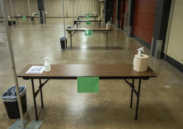 Tables with cleaning spray are spaced apart in a large room.