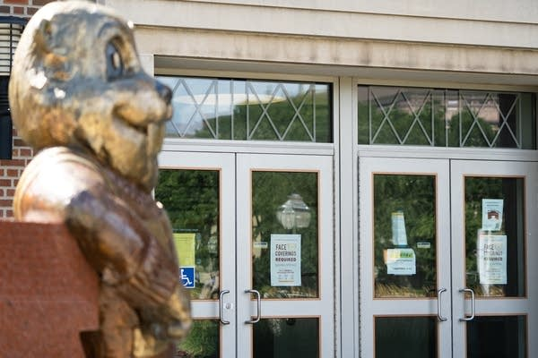 A gold statue of a gopher stands in front of doors with signs.