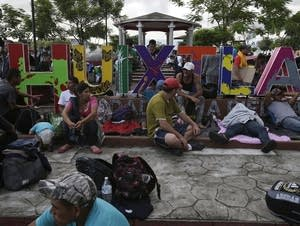 Central American migrants making their way to the U.S. rest in a park.