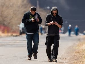 Two men walk away after capturing images of the smoke plume.