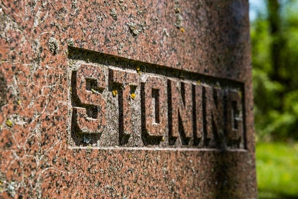 """""""Stoning"""" in carved into a headstone."""