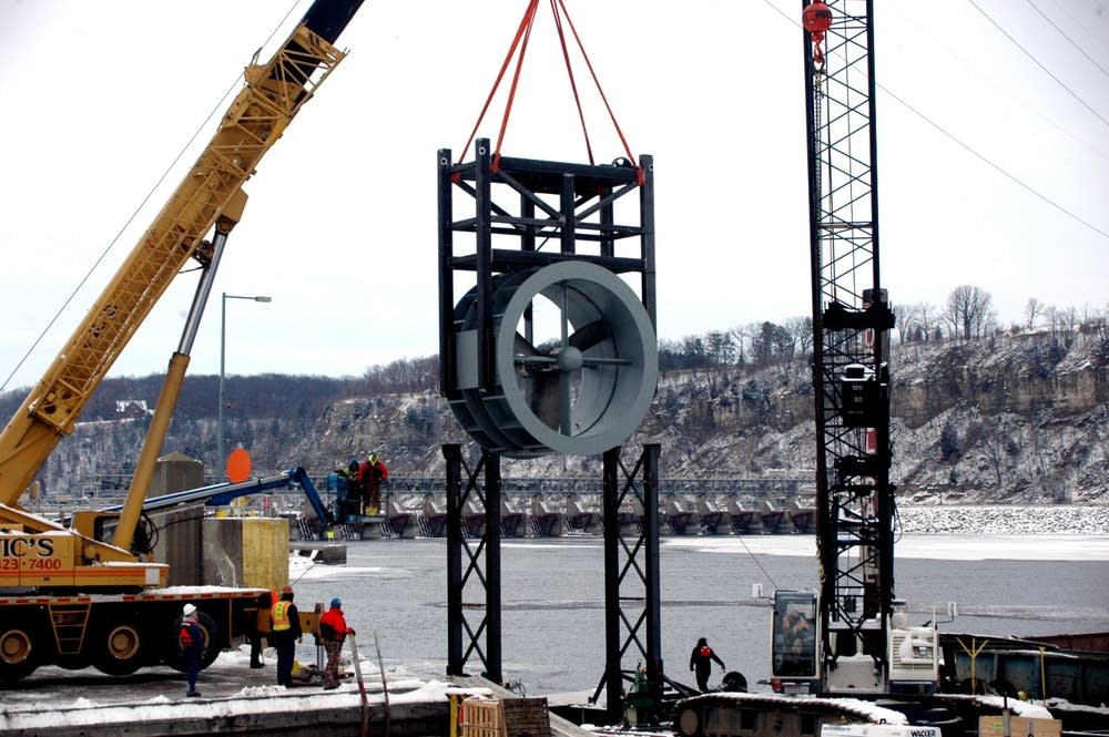 Workers install a hydrokinetic turbine