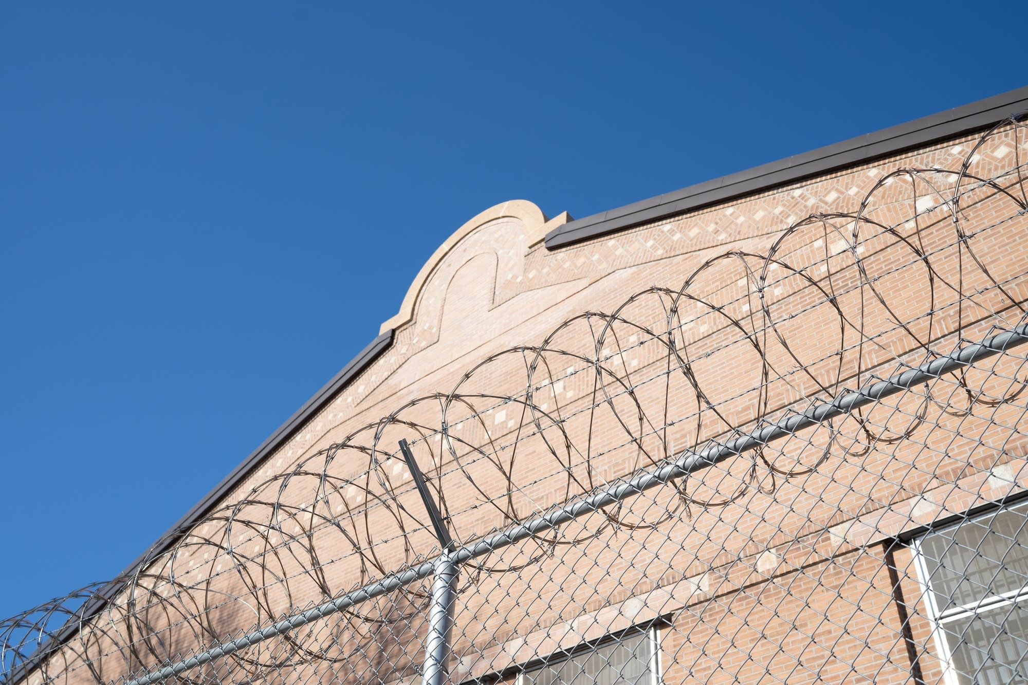 Barbed wire tops a fence separating two parts of Stillwater prison.