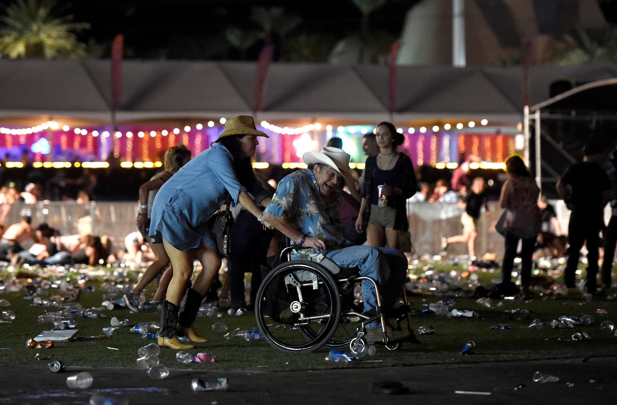 A man in a wheelchair is taken away from the country music festival.