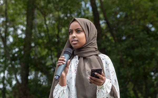 A young woman wearing a hijab speaks into a microphone.
